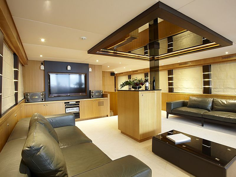 yacht cabin with television and long black couches and low table