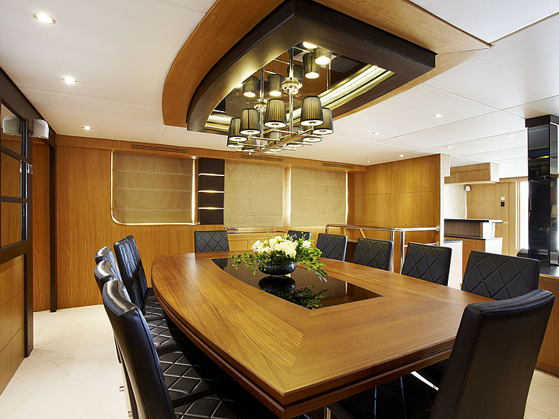 medium size meeting room in yacht with long wooden table and black chairs