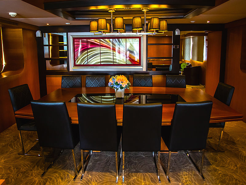yacht business meeting room with wooden long table and pendant lights