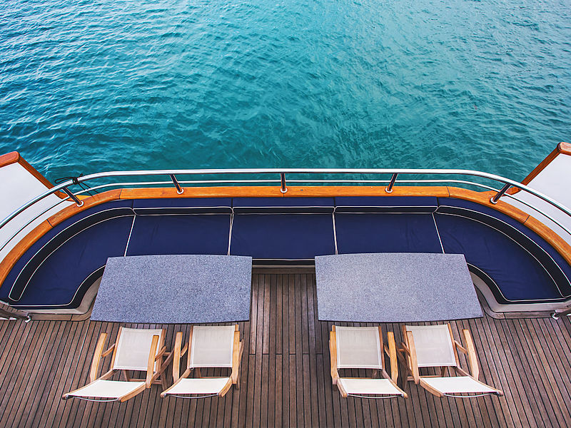 yacht lower deck area with blue couch and tables