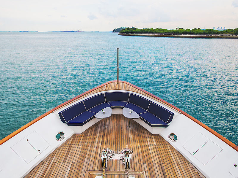 yacht bow area with blue round couch and small table