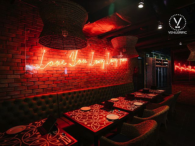 restaurant with neon light wording and long couch