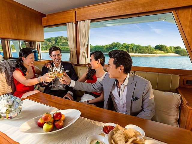 people celebrate their friends birthday in yacht cabin area with champagne