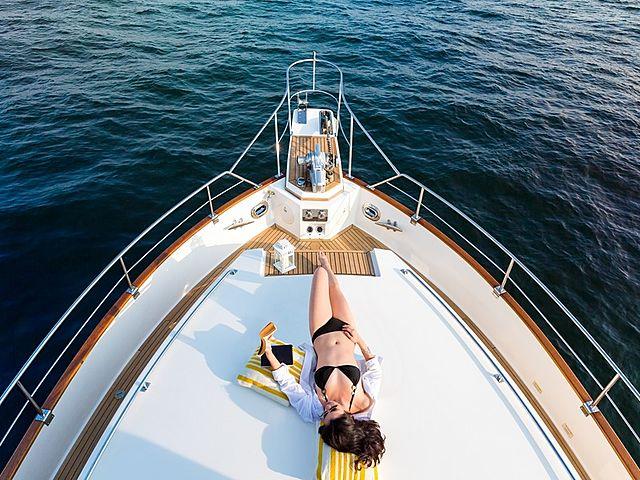 a woman with bikini do sunbathing on yacht bow area