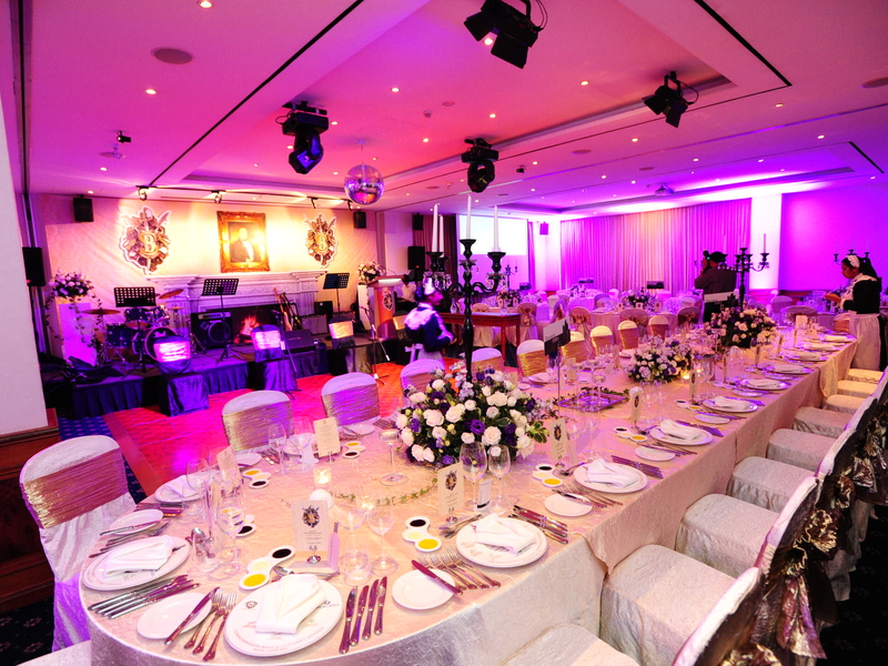 white event space in singapore with long dining table and mini stage
