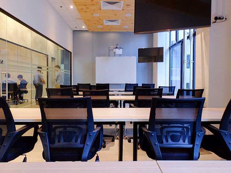 glass seminar room with projector screen and classroom layout