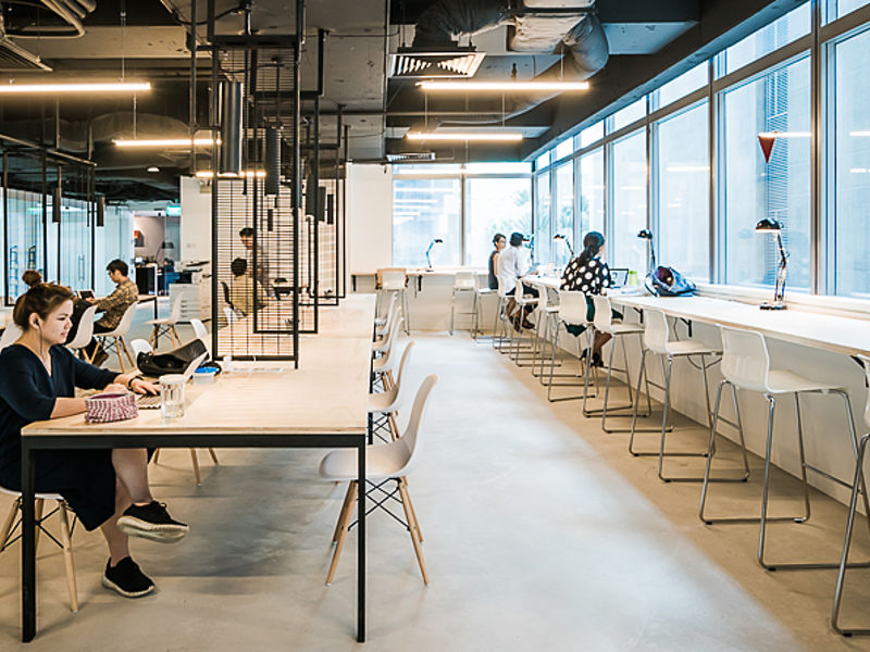 people sitting in coworking space's shared desk area with white table set