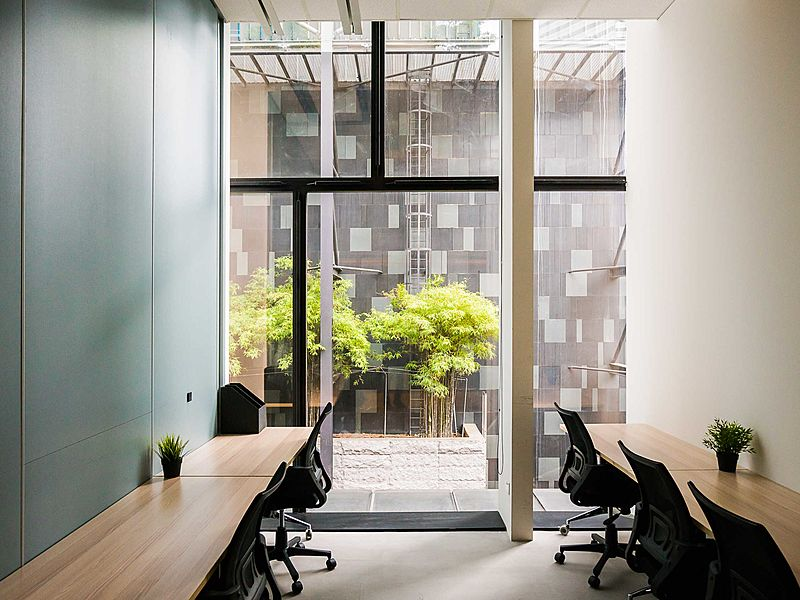 coworking space's private office with long tables and fixed window