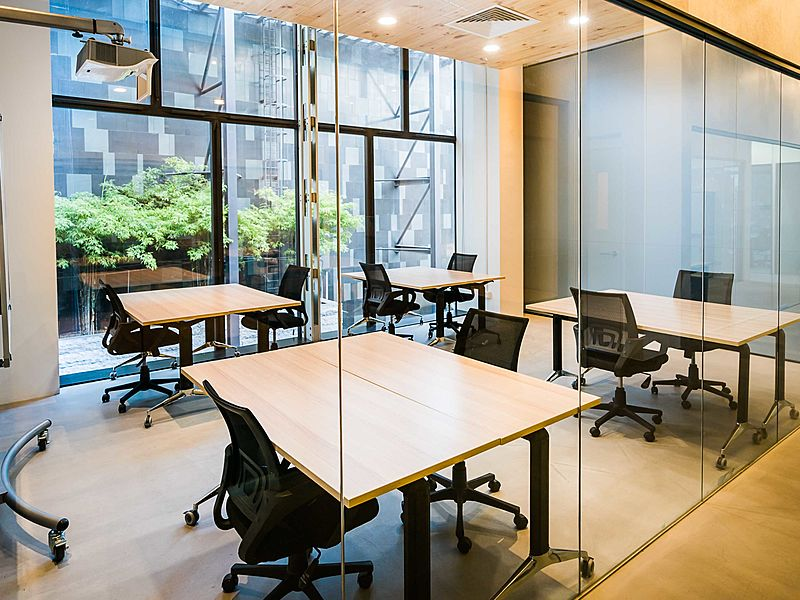 glass private office in coworking space with projector