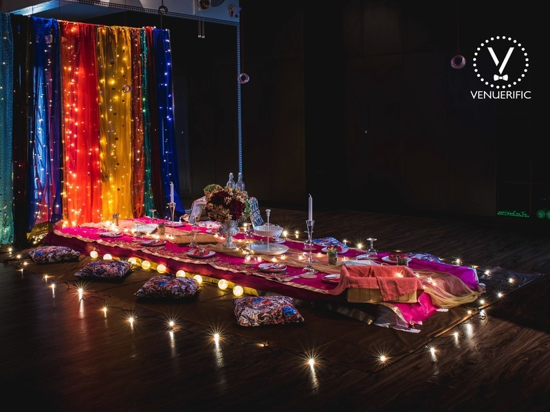 colourful indian wedding venue in singapore decorated with low table and candle lights