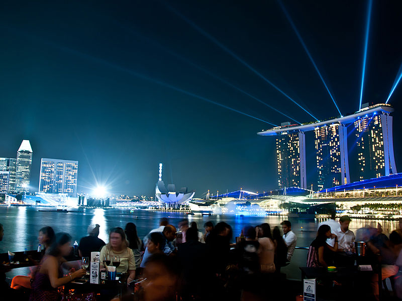 people are enjoying the night with the view of marina bay