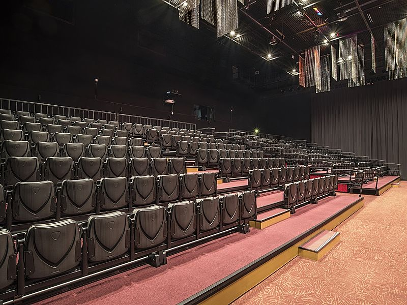 small theater with black tiered seating