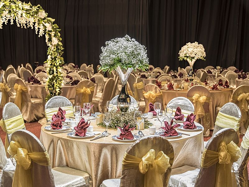 wedding guests table decorated with golden cover and flower vase