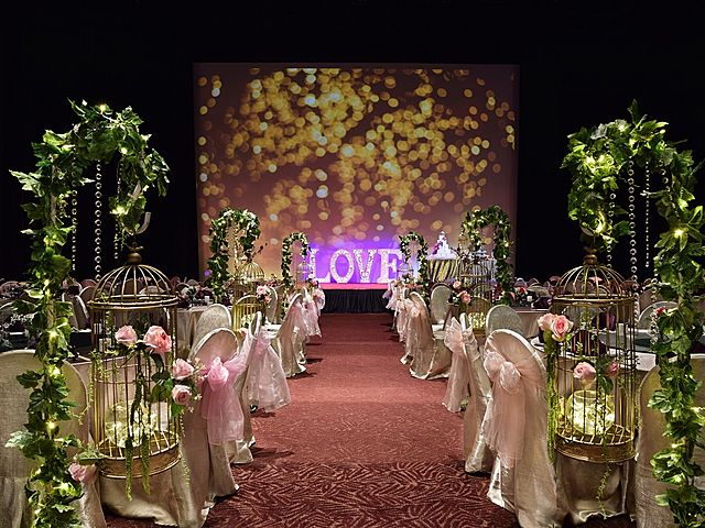 wedding banquet hall decorated with plants and giant screen