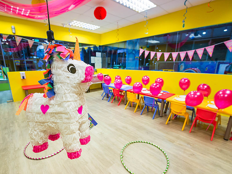 horse pinata hanging on yellow birthday party room