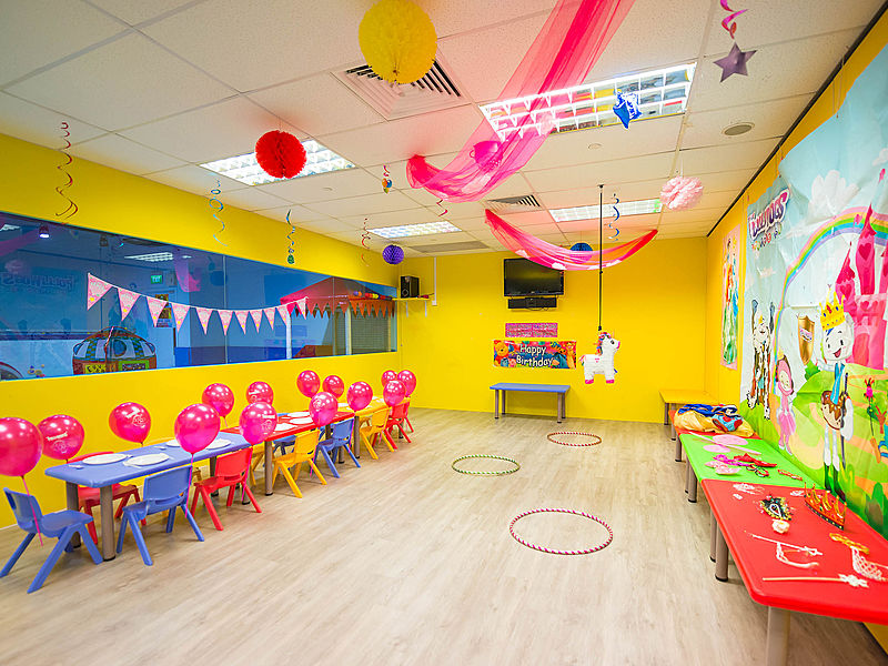 yellow-themed kids birthday venue with unicorn pinata and game stations