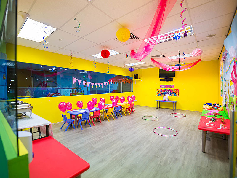 small kids birthday celebration venue with yellow wall decorated with paper crafts