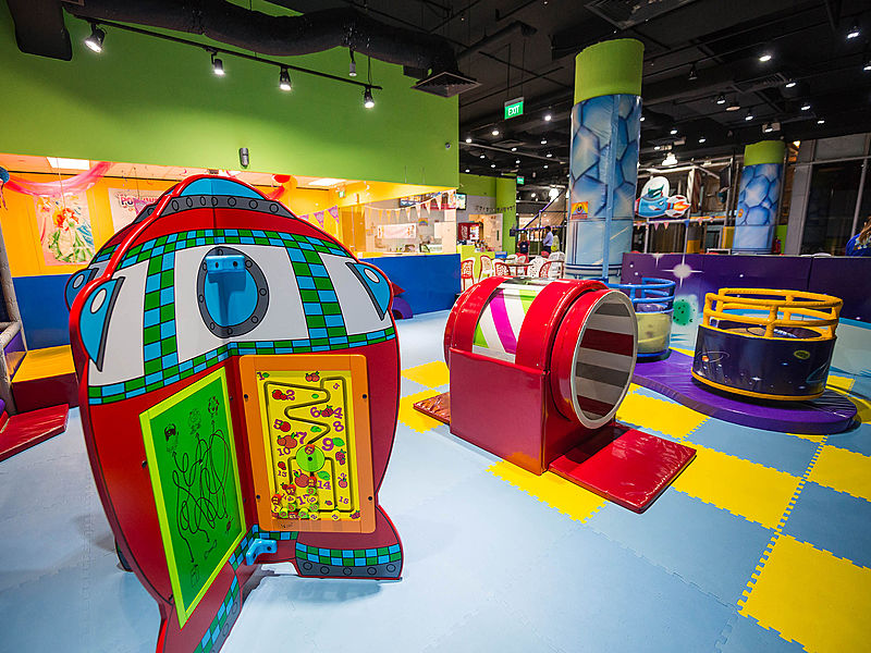space themed indoor playground with puzzle mat and several game stations