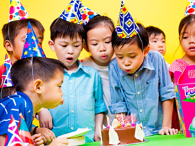 kids wearing birthday caps and blowing candles together