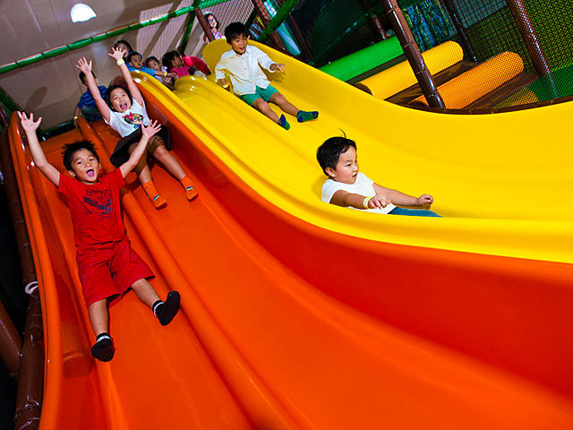 the children glide together on the red and yellow playground slide