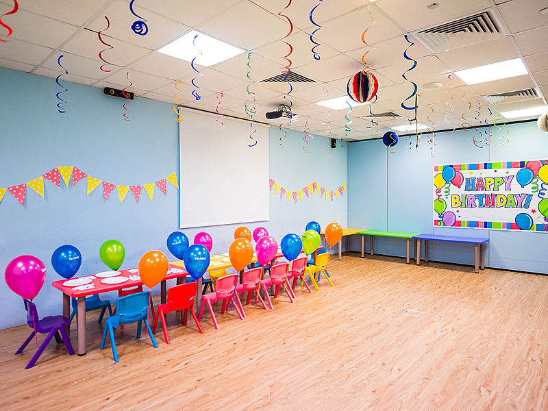 kids birthday celebration venue with table set up and a big screen