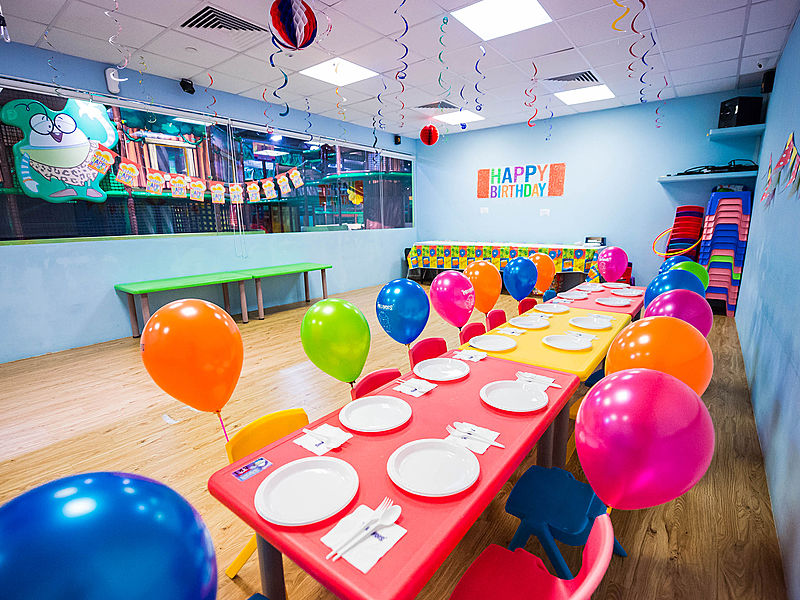 blue-themed birthday party room with balloons on the chairs