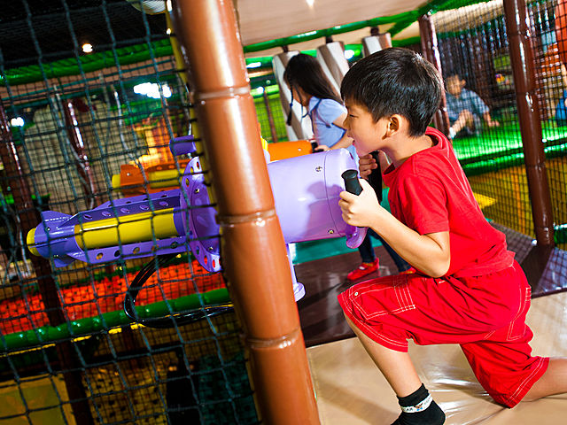 kids playing with purple ball gun in indoor playground