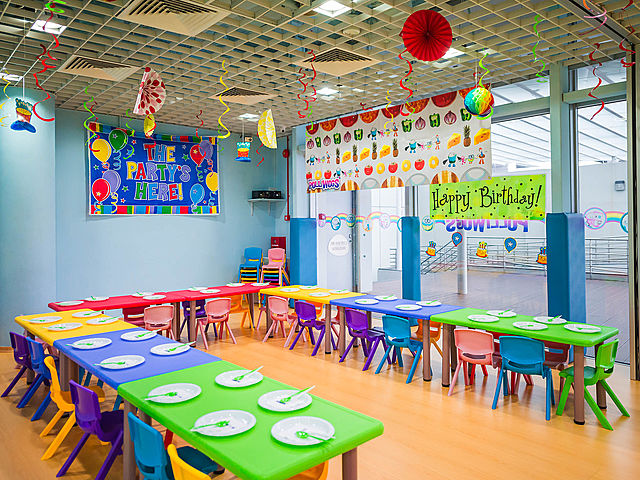 kids birthday party room with colourful u-shaped seating and crafts decoration