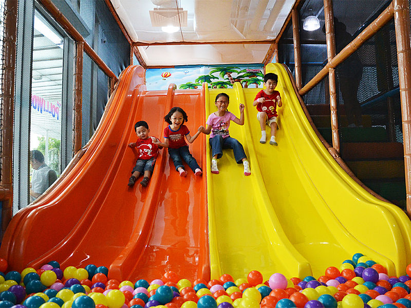 kids slide together into the ball pit in playground