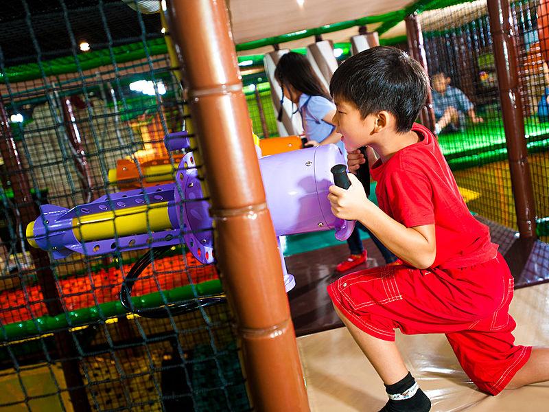 redshirt boy playing with a ball gun in playground