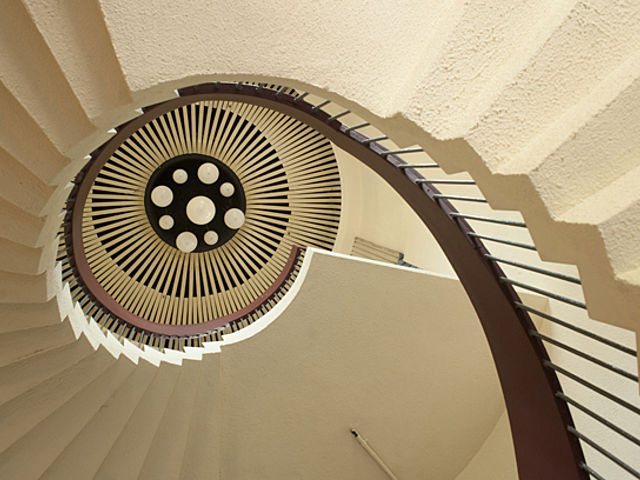 white spiral stairs with dark brown holders