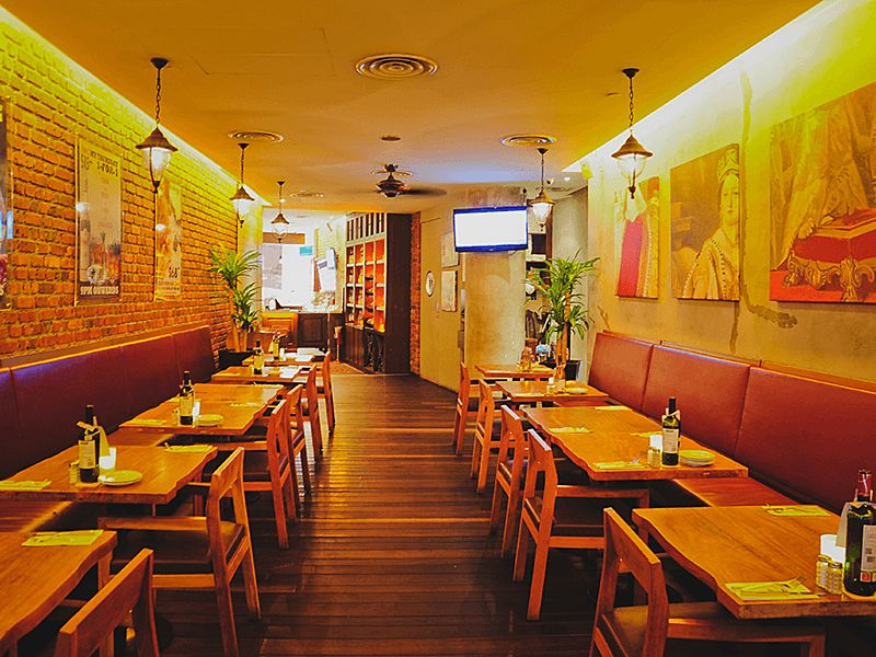 restaurant dining room with wooden floors and wall paintings