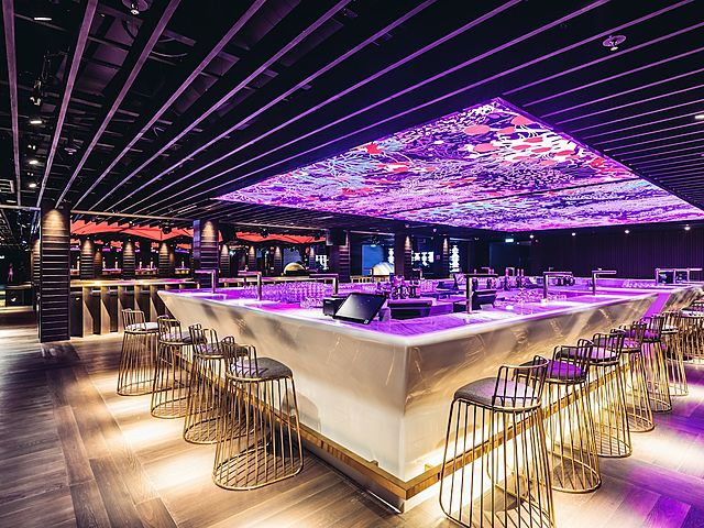 bar with purple ceiling and golden bar stool