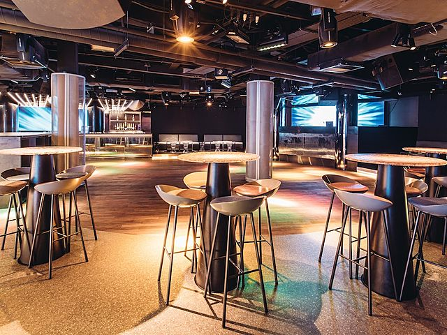 a large room with several round bar tables and bar stools