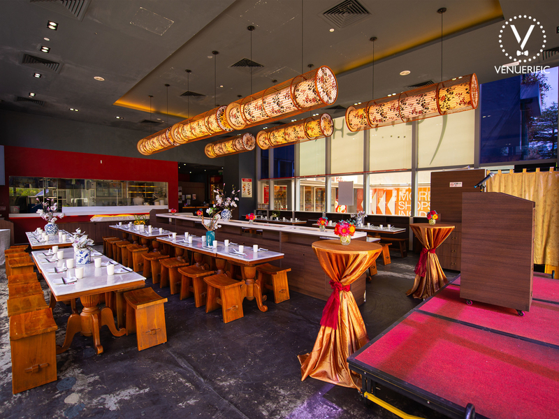 changi networking venue with several brown square tables and cocktail tables