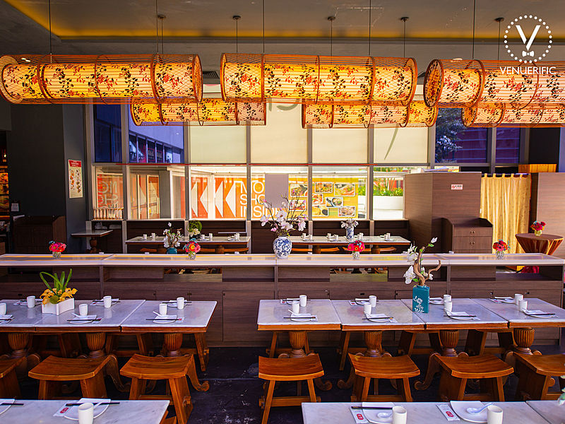 restaurant with a long white table and brown wooden saddle seat stool