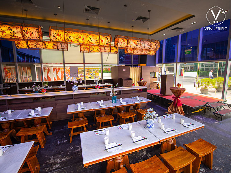 high ceiling restaurant with red mini stage