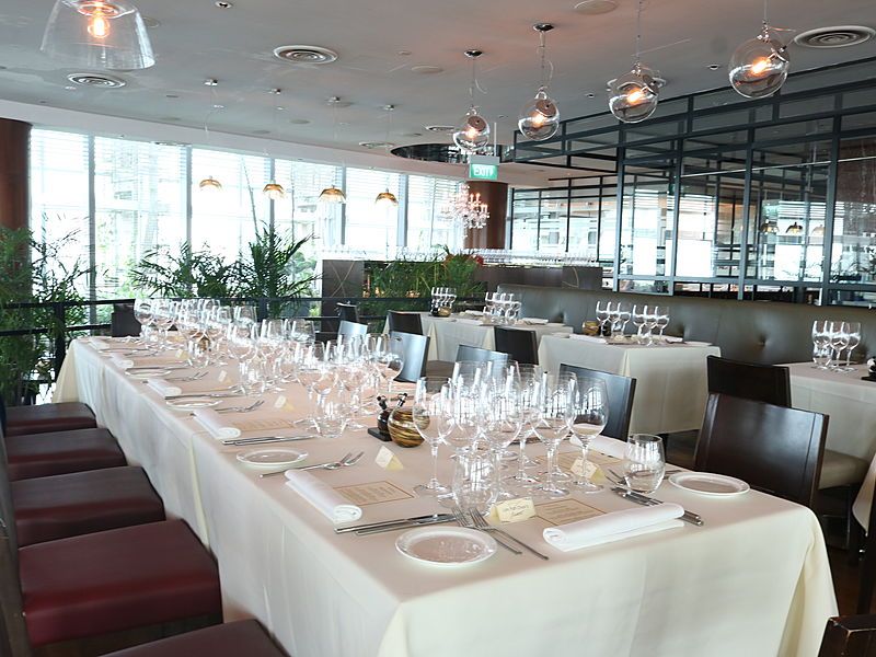an italian restaurant with long white tables and maroon chairs
