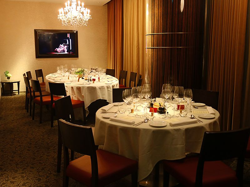 small fine dining room with chandelier and television