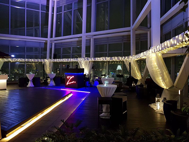 large glass room with high ceiling and cocktail tables