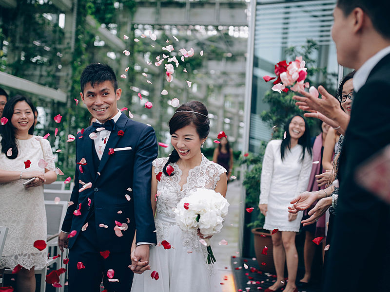 bride and groom walking in the wedding aisle with flower shower from the guests