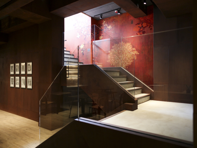 staircase to the next floor with red and golden tree wallpaper