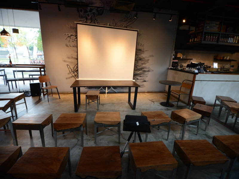 corporate seminar setup with giant screen and theatre chair setting