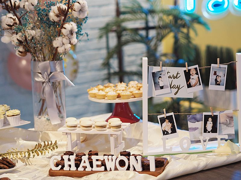 dessert station decorated with baby's photo and flowers