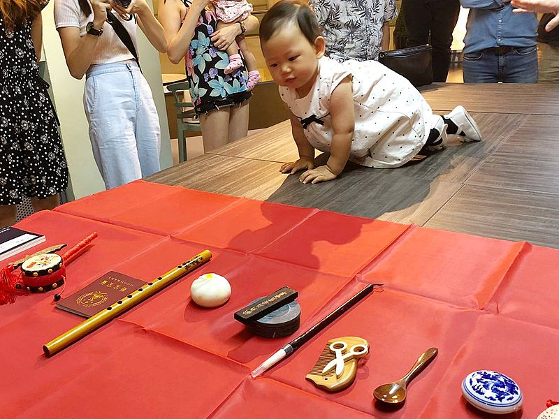 a child is crawling toward stuffs at a doljanchi event