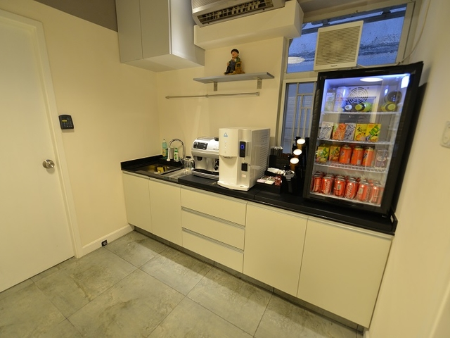 pantry area equipped with coffee maker and cold drinks inside the refrigerator