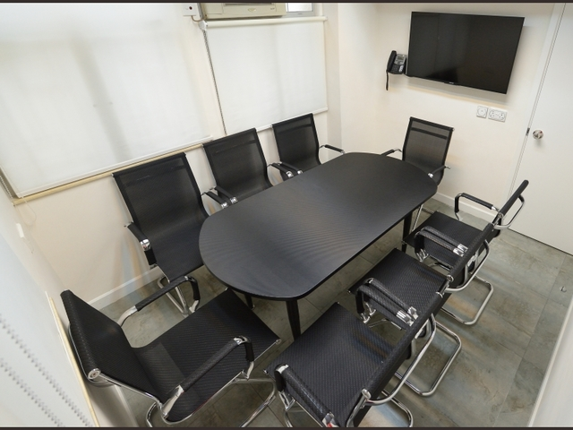 private meeting room for 8 people with tv screen on the wall