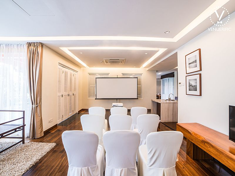 corporate event set up in private mansion with white chairs screen projector