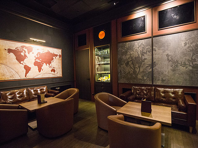 whisky lounge with brown couch and paintings on the wall