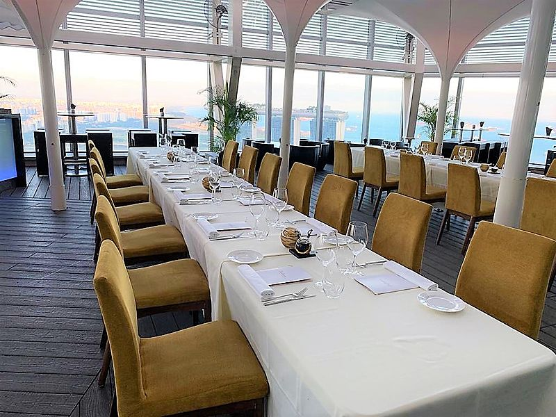 a long white table in a large glass dining room with sea view